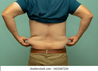 full man holds his hand folds of fat on their sides, view from behind