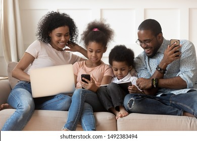 Full mixed-race family sit on couch having bad habit devices overuse addicted with electronic gadget laptop smartphone and tablet users spending lazy weekend at home, dependence of modern tech concept
