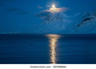 Full moon above snowy mountains during a night in eastern Iceland.