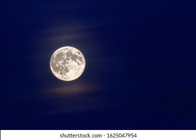 Full Moon with clouds in the blue sky