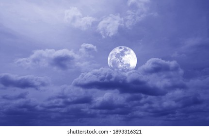 The full moon in the clouds optimize to cool tone. The sky and the moon taken from camera.