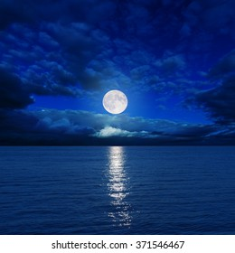 full moon in clouds over dark water with reflections on it