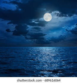 full moon in clouds over sea in night