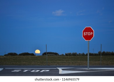Full moon coming out on a road in the countryside next to a stop sign