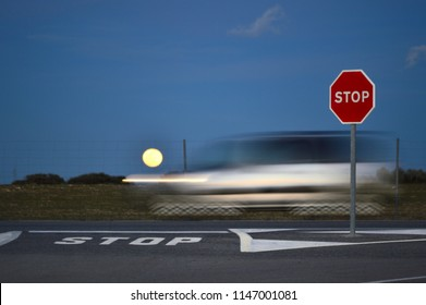 full moon coming out on a road in the countryside next to a stop sign with speed car