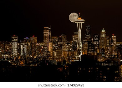 A full moon in display behind the skyline of Seattle, Washington.