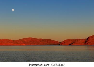 Full moon during sunset over Lake Argyle