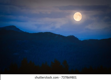 Full moon in dusk over dark mountains with clouds in background and forest in foreground