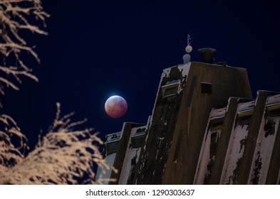Full moon eclipse above old factory building in snowy winter. Toppila district in Oulu, Finland.