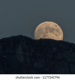 Full Moon Emerges Behind Mountain Ridge