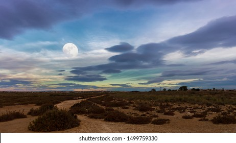 The full moon is in the evening in January after sunset over the land on the salt lake of the Spanish city of Torrevieja. It is very cloudy and windy. The clouds in the sky look wild and dark.