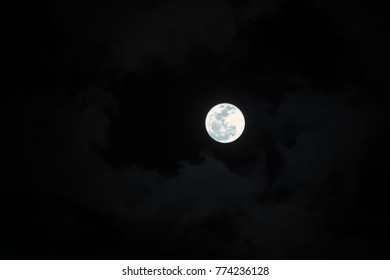 Full moon with fluffy clouds in the sky