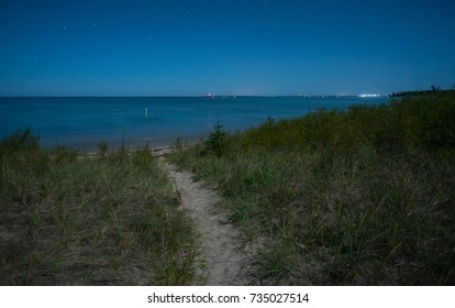 Full moon light reveals a deep blue sky, stars, and a trail to the Lake Michigan beach.