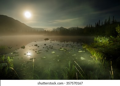 Full Moon lightens foggy Polygonal lake in northern taiga forest before Aurora Borealis starts in Kunijok valley, Hibiny mountains above the Arctic Circle, Russia