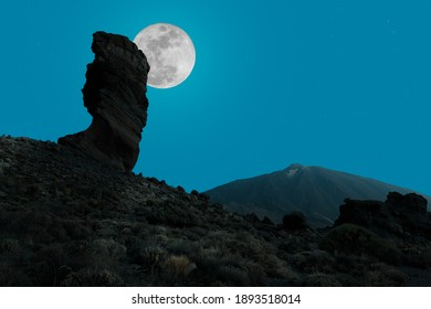 The full moon at night behind the impressive free-standing rock cinchado on the Spanish Atlantic island of Tenerife. On the right is the highest mountain in Spain, the Teide.