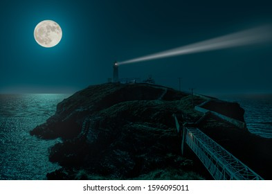 A full moon night at the South Stack lighthouse on the Irish Sea. The moonlight is reflected by the sea. The light beam can be seen. At the end of the bridge there is light in the tunnel.