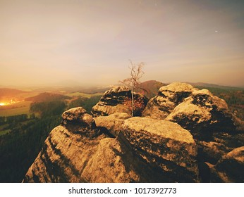 Full moon night with sunrise in a beautiful mountain of Bohemian-Saxony Switzerland. Sandstone peaks and hills increased from foggy background. First sun rays.