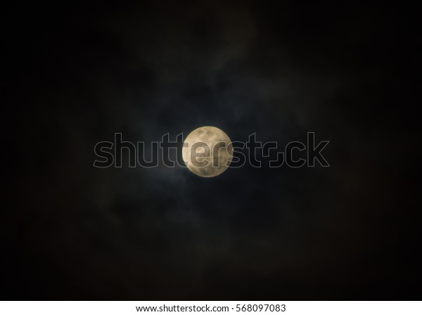 Full moon on cloudy black sky as background