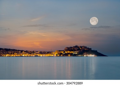 Full moon over the citadel of Calvi in the Balagne region of Corsica at dusk with reflections of light across a calm mediterranean sea