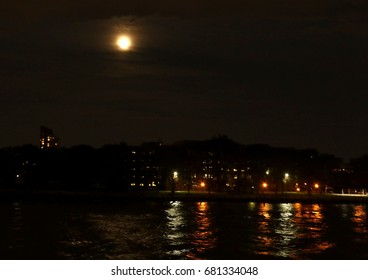 Full moon over East River with city lights