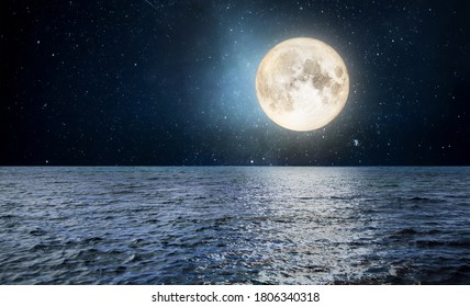 Full moon over the sea at night starry sky. Moonlight landscape.