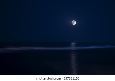 Full moon over the sea at night with water reflection, or moonlight moon road on sea, dark blue sky