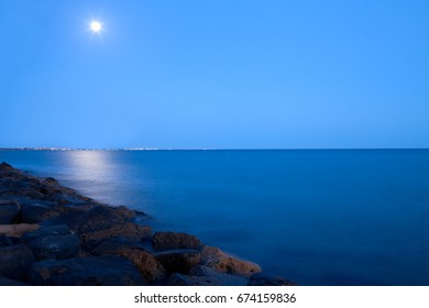 Full moon over the sea at night, long exposure shot with copy space available.