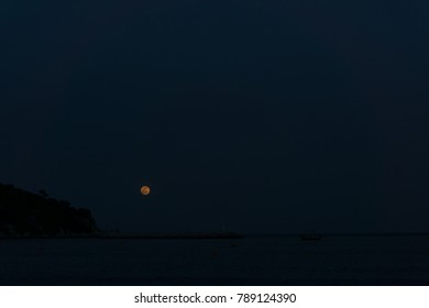 full moon over the seascape and mountain at night.