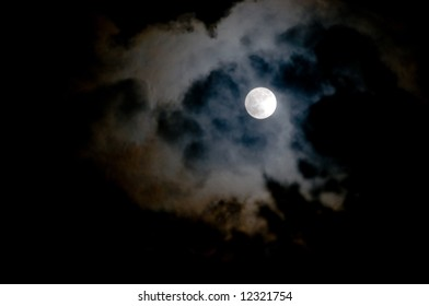 full moon peeks through a hole in layers of ominous, dark clouds at night