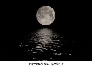 Full moon reflected water over dark black sky at night