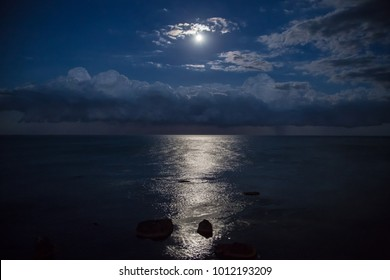 Full moon and reflection in sea, beautiful clouds.