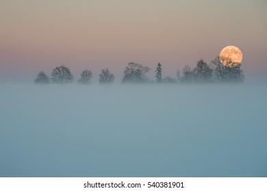 Full moon rise in fog