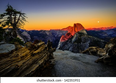 A full moon rises behind iconic Half Dome at sunset from Glacier Point in Yosemite National Park, California.