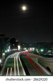 A full moon rises over a highway running through Washington DC.