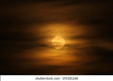 A full moon rises through the orange clouds of evening in Uganda, Africa
