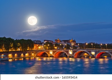 Full moon rising above illuminated ancient Pont Neuf bridge in Toulouse, France