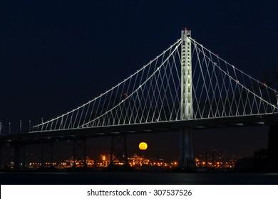 The full moon rising behind the new Oakland Bay Bridge at night.