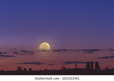 Full Moon rising from the city panorama silhouettes. My astronomy work.