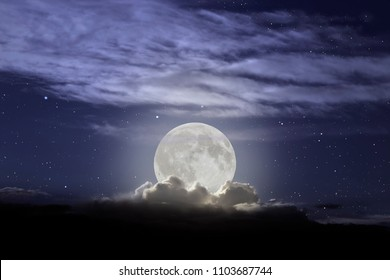 Full moon rising in a cloudy night.
