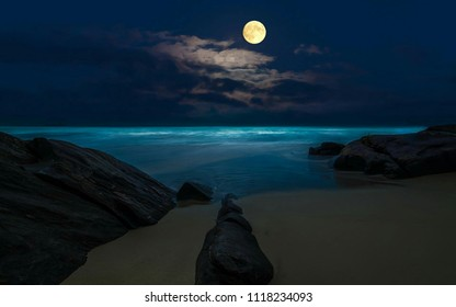 Full moon rising over empty ocean on the rock beach front at night with copy space.A night panorama view of crescent moon in the night sky at midnight. Moonlight romantic landscape background concept.