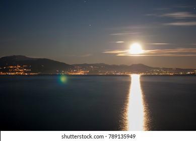 Full moon rising over lake.