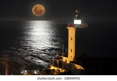 Full moon rising over ocean with lighthouse