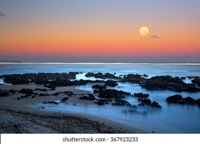The full moon rising over the ocean as the sun sets and the sky turns pink and yellow on a cloudless evening over the island of Guam