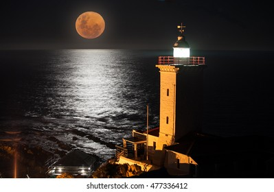 The full moon rising over the sea with a lighthouse in the fore ground