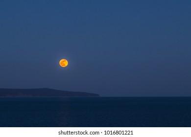 Full moon rising over the seashore