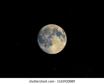 Full moon seen with an astronomical telescope, with starry sky