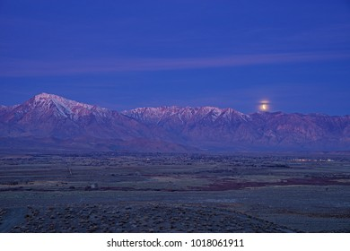 the full moon sets during an eclipse over the Wheeler Crest and Bishop California