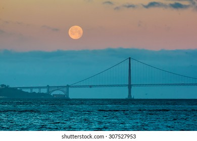 The full moon setting behind the Golden Gate Bridge and the fog just before sunrise.