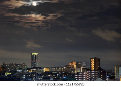 Full moon shines bright over urban homes and apartments in Osaka, Japan
