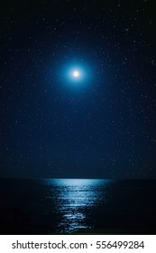 the full moon in the starry sky ,the moonlight on the sea, calm sea and reflection in water